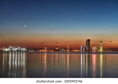 Beautiful night Cityscape, view of city Batumi at sunset from sea side. Night reflections of lights in Black Sea port of Batumi, capital of Adjara. Georgia.