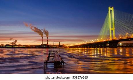 Beautiful night Kiev city and winter river with illuminated bridge and long exposure traffic light, Kyiv, Ukraine