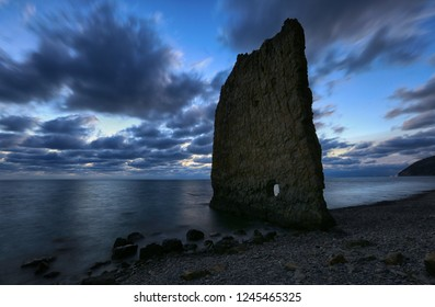 Beautiful night landscape on the coast. Evening sky, natural rock in the form of sail, sea and clouds
