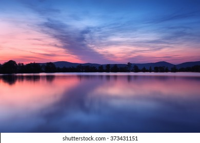 Beautiful night landscape on the mountain lake with stars and reflected clouds in water in spring. Colorful sky.  Nature background