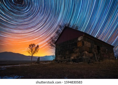 Beautiful night landscape, small church and star trails. The colorful star trails on the sky with orientation on the north star. Night time lapse photography.