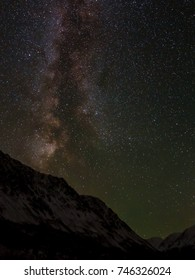 Beautiful night landscape with stars and the Milky Way on a dark night sky over mountains covered with snow