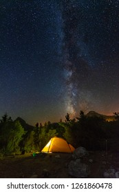 Beautiful night landscapes in the Turkish Taurus Mountains, with the bright glow of the Milky Way, against the background of tourists and the yellow tent in the night sky.