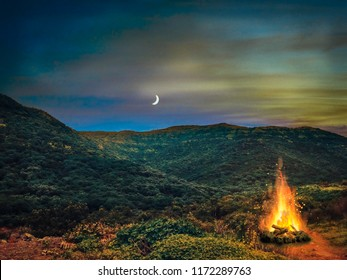 A beautiful night outdoor campfire surrounded by mountains with sunset sky and moon.