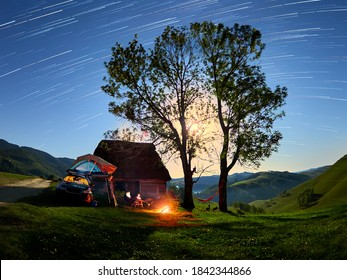Beautiful night scene startrails with a family camping with a car and a tent and camp fire in the wild Apuseni mountains, Transylvania, Romania