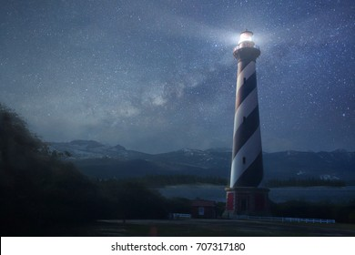 A beautiful night sky behind a shining lighthouse