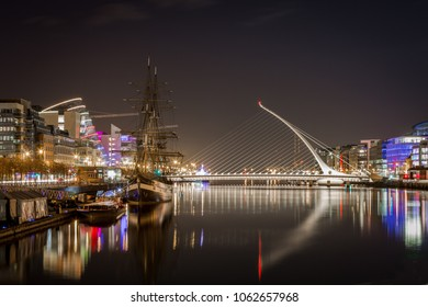 Beautiful night view of Dublin with water, bridge and buildings.