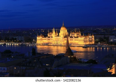 Beautiful night view of the Hungarian Parliament building and the Danube river with lights in the water in Budapest, Hungary