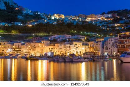 Beautiful night view of Marina Grande, Capri island, Italy. Illuminated streets of city are reflected in serene sea. Photo taken witn long exposure.