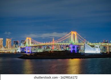 Beautiful night view at Odaiba Marine Park / Daiba artificial island at Tokyo Bay ,with light up illumination of Rainbow bridge and Tokyo Tower,  famous landmark of Japan in January 2020