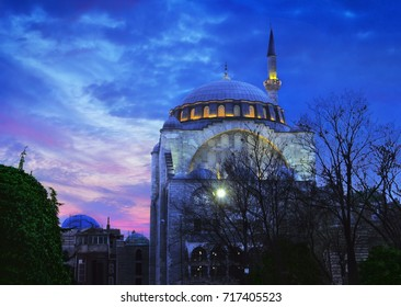 Beautiful night view of Old Mosque in Byzantine style with one minaret, architectural facade illumination against the background of colorful blue and pink sunset sky in Sultanahmet, Istanbul, Turkey