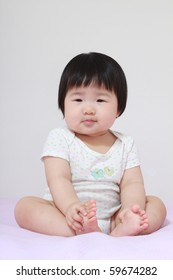 Beautiful Nine Month Old Asian Baby Infant Girl Sitting Dociley with both hands grasping feet
