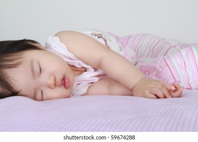 Beautiful Nine Month Old Asian Baby Infant Girl sound asleep lying sideways on pink bedsheet