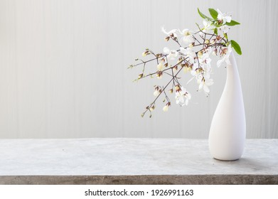Beautiful Nodding Clerodendron flowers in modern vase set on concrete table with white wood background with copy space, soft tone still life