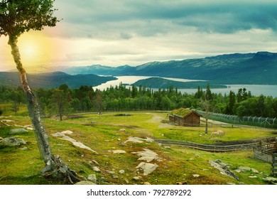 Beautiful nordic scenery with forest, mountains, lake and house with green grass or living roof. Mountain and valley landscape