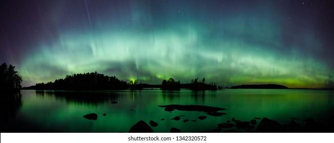 Beautiful northern lights aurora borealis over lake in Finland panorama
