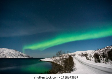 Beautiful Northern Lights near Tromso, Norway. Reflection on the water
