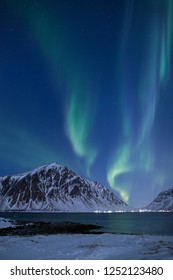 Beautiful northern lights over the snow covered winter landscape of the Lofoten islands