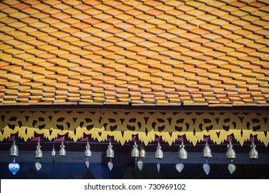 Beautiful northern Thai style temple's roof tiles and eaves details with cute small bronze bells. Decorative small bronze bells are hanging on the roof of thai temple, at Northern of Thailand.