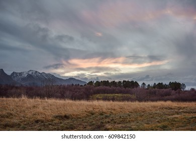 Beautiful Norway landscape at sunset: grass field with trees and mountains on background with colorful cloudscape