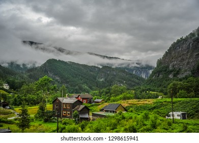 Beautiful Norway nature landscape with small house and village in the middle of valley surrounded by green hills and mountain