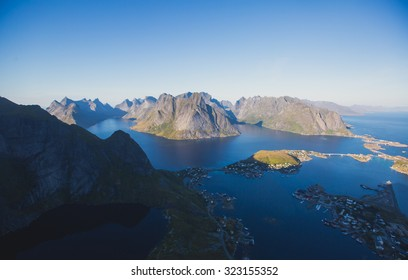 Beautiful norwegian landscape with famous top peak Reinbringen, Lofoten Islands, with a group of hikers tourists, and with a view on famous fishing village Reine, Moskenesoya and norwegian sea