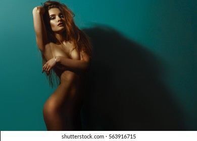 beautiful nude girl stands in the Studio covering breasts with her hand and the second hand keeps for hair