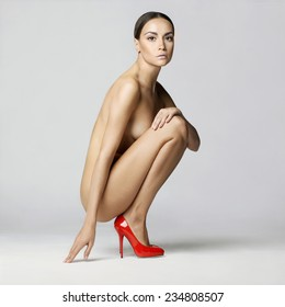 beautiful nude lady with perfect body sits in red shoes. Conceptual fashion art photo