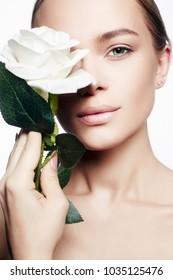 Beautiful Nude Make-up Woman with Flower. Beauty Portrait of girl with White Rose Flower. Clean Face, care