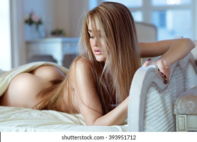 Beautiful nude sexy lady in elegant pose. Portrait of fashion model girl indoors. Beauty blonde woman with attractive buttocks. Close-up female ass and naked body