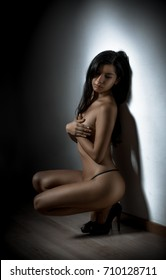 beautiful nude woman in a light spot on a dark background