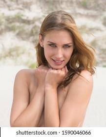 Beautiful nude woman  posing on sea beach