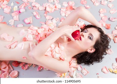 beautiful  nude woman with roses eating an apple