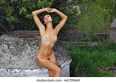 Beautiful nude woman in summer evening forest with dot.