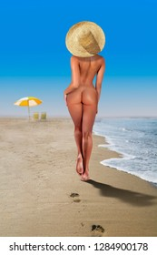 Beautiful nude woman walking on the beach in sunny day with deck chairs and umbrella on blurred background. Attractive sexy tanned body in a nature, beauty and purity concept
