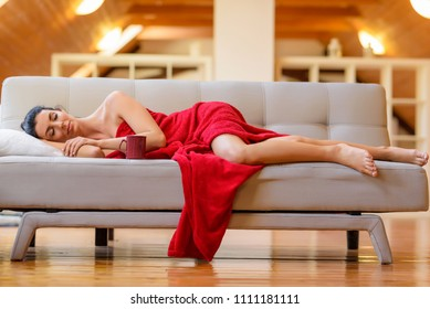 A beautiful nude woman wrapped in a cozy blanket relaxing on the sofa in a Loft Apartment.
