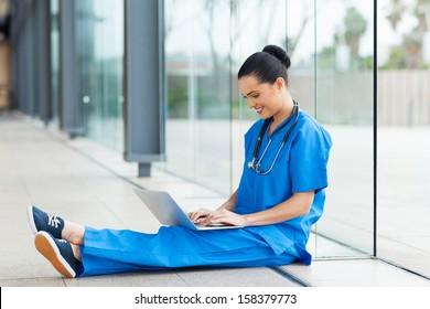 beautiful nurse sitting on floor and using laptop computer during break