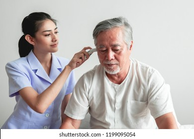 Beautiful nurse using high tech Temperature measurement tool on old man. Senior Asian man with white beard in bed with attractive asian woman nurse. Senior retirement home service, care taker concept.