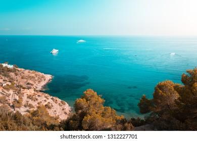 Beautiful ocean coastline in Ibiza island, part of Balearic archipelago in Spain. Orange and teal view