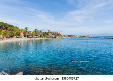 Beautiful ocean landscape view. Tourists swimming in turquoise water of Atlantic Ocean. Sand beach and palm trees on blue sky background. Willemstad. Curacao.