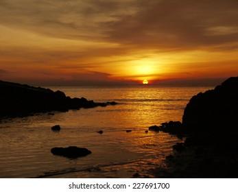 Beautiful ocean sunrise - calm sea and boulders stone coastline with unusual light