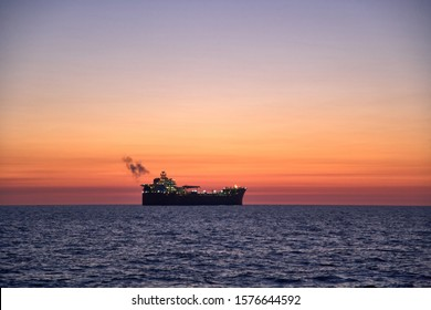Beautiful  ocean sunset, with colorful clouds, dark waves and silhouette of ship, oil tanker on the horizon with smoke coming from the ships exhaust pipe.