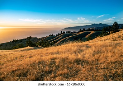 Beautiful ocean view of Central California coastline in Big Sur. Dry golden grass lights up in afternoon sun with rolling hills and coastal mountains reaching the Pacific Ocean.