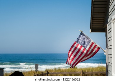 A beautiful oceanfront property with a classic American flag on the side of it with the coastline in the background.