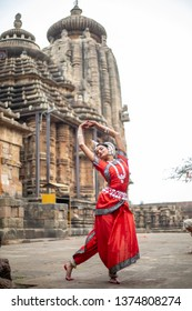 Beautiful Odissi dancer striking pose against the backdrop of Ananta Basudeva temple with sculptures in bhubaneswar, Odisha, India