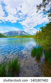 Beautiful Offensee lake landscape with mountains, forest, clouds and reflections in the water in Austrian Alps. Salzkammergut region.