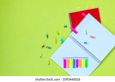 Beautiful office stationery flat lay with ruled red and yellow notebooks, stationery and office supplies and paper clip on the bright desk with green background.