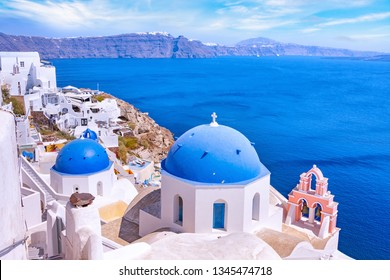 Beautiful Oia town on Santorini island, Greece. Traditional white architecture  and greek orthodox churches with blue domes over the Caldera, Aegean sea. Scenic travel background.