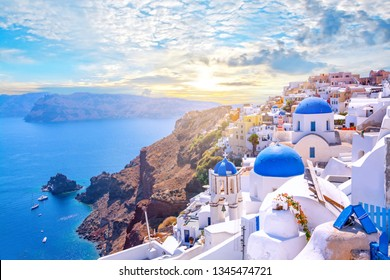 Beautiful Oia town on Santorini island, Greece. Traditional white architecture  and greek orthodox churches with blue domes over the Caldera, Aegean sea. Scenic travel background. - Shutterstock ID 1345474721
