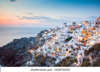 beautiful Oia town on Santorini island, Greece. Traditional white architecture and greek orthodox churches with blue domes over the Caldera, Aegean sea, Scenic travel background